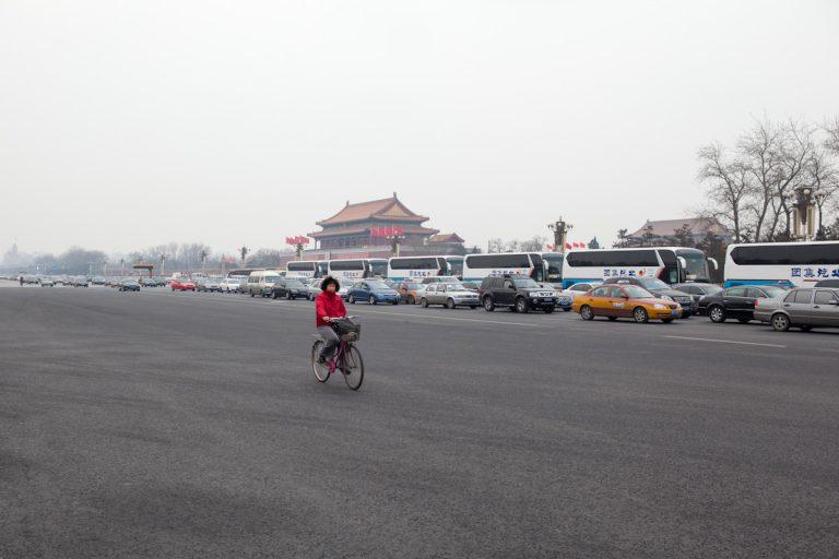Während die Autos im Stau stehen, hat eine Radfahrerin hat die Chang'an Avenue vor dem Platz des Himmlischen Friedens für sich allein. Die Chang'an Avenue führt am Tor des Himmlischen Friedens vorbei, auf der auch große Paraden stattfinden. Peking - China