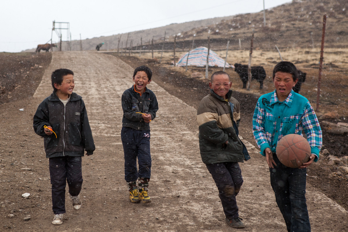 Vier Jungen kommen von einem Fussballspiel auf einer Dorfstraße entlang. Es hat gerade angefangen zu schneien. Langmusi - Gansu - China