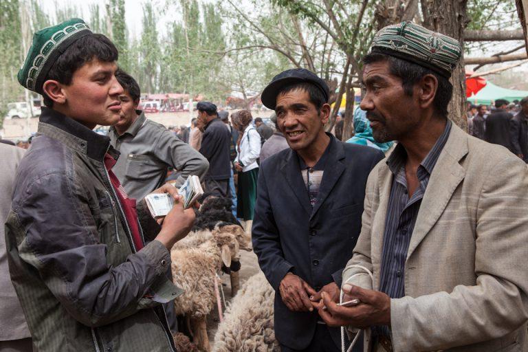 Drei Händler tauschen sich auf dem Viehmarkt in Upal aus. Der Ort liegt entlang des Karakorum-Highway und etwa  50 Kilometer von Kashgar entfernt. Upal - Xinjiang - China