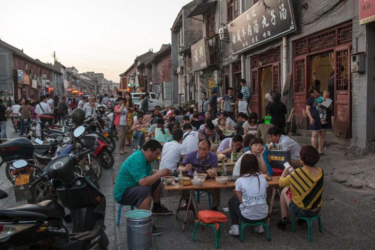 Eine Straße in Luoyang ist voll mit Tischen und kleinen Stühlen, an denen Kundschaft zu Abend isst. Luoyang - Henan - China
