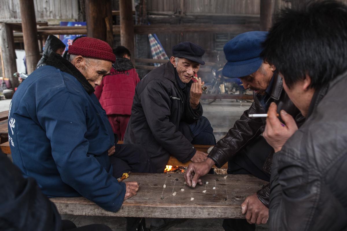 Auf einer Sitzbank aus Holz ist die chinesische Variante des Spiels Mühle eingearbeitet. Unter einer Überdachung spielen zwei Männer gegeneinander und mehrere schauen ihnen zu. Zhaoxing ist ein Dorf im autonomen Bezirk Qiandongnan, in der die Minderheiten der Miao und die Dong leben, in der Provinz Guizhou im Südwesten Chinas. Zhaoxing - Guizhou - China