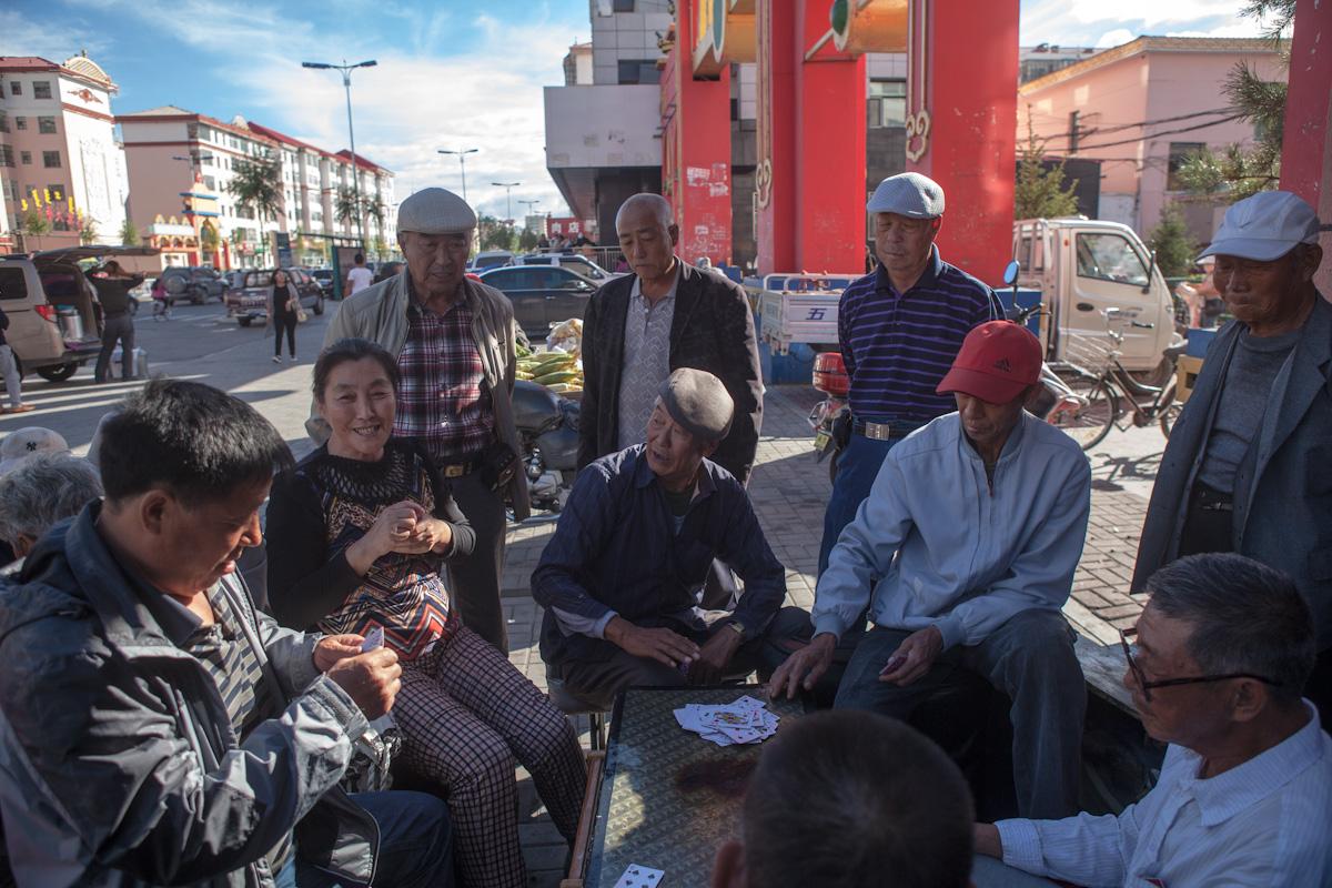 Ein Tisch und mehrere Sitzgelegenheiten, schon kann es losgehen. Viele Aktivitäten finden draußen, im öffentlichen Raum, statt. Mehrere Anwohner sitzen in einem Wohnviertel in Hulun Buir beim Karten spielen um einen Tisch, weitere Anwohnern stehen dahinter und schauen zu. Hulun Buir liegt als Teil der Mandschurei im äußerten Nordosten Chinas, unweit der Grenzregion zu Russland und der Mongolei. Hulun Buir - Innere Mongolei - China