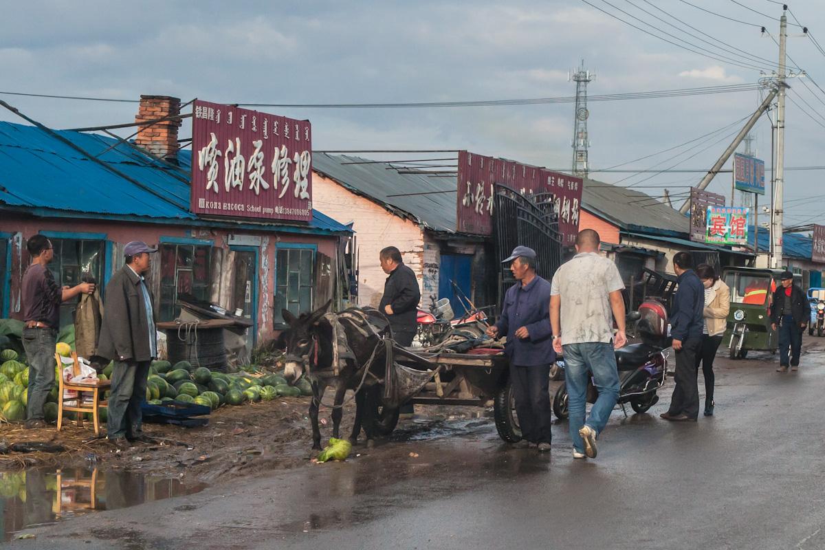 Händler verkaufen Melonen an einer Straße in Ergun, wo es zuvor noch stark geregnet hat. Die Beschriftung auf der großen Hinweistafel am Haus hinter den Händlern, ist neben chinesisch auch auf mongolisch und russisch. Ergun liegt nördlich von Hulun Buir, im äußerten Nordosten Chinas, in der Grenzregion zu Russland und der Mongolei. Ergun - Innere Mongolei - China