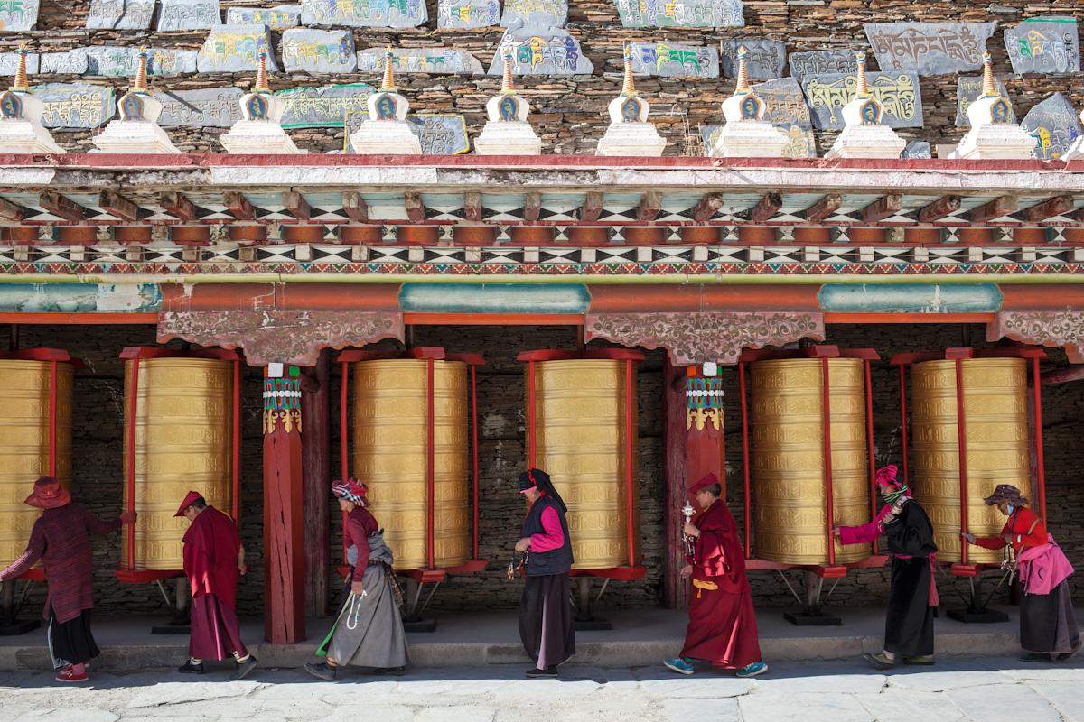 Gläubige drehen die Gebetsmühlen an der Mani Steinwand. Jiagulong und Ani Gompa - Autonome Präfektur Garzê Tibet - China
