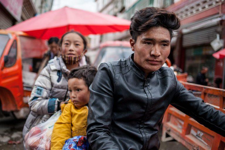 Die Familie fährt mit dem Motorrad durch den Markt in Garzê. Autonome Präfektur Garzê Tibet - China