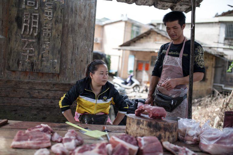 Der offene Stand der Fleischerei befindet sich direkt an einer Straße im Dorf. Die Verkäuferin wurde gerade von dem Mann beliefert. Gegen Ungeziefer liegt auf dem Tisch eine Fliegenklatsche. Yunshuiyao liegt im Süden der Provinz Fujian, eine Region in der sich viele Tolou-Lehmrundbauten befinden. Yunshuiyao - Fujian - China