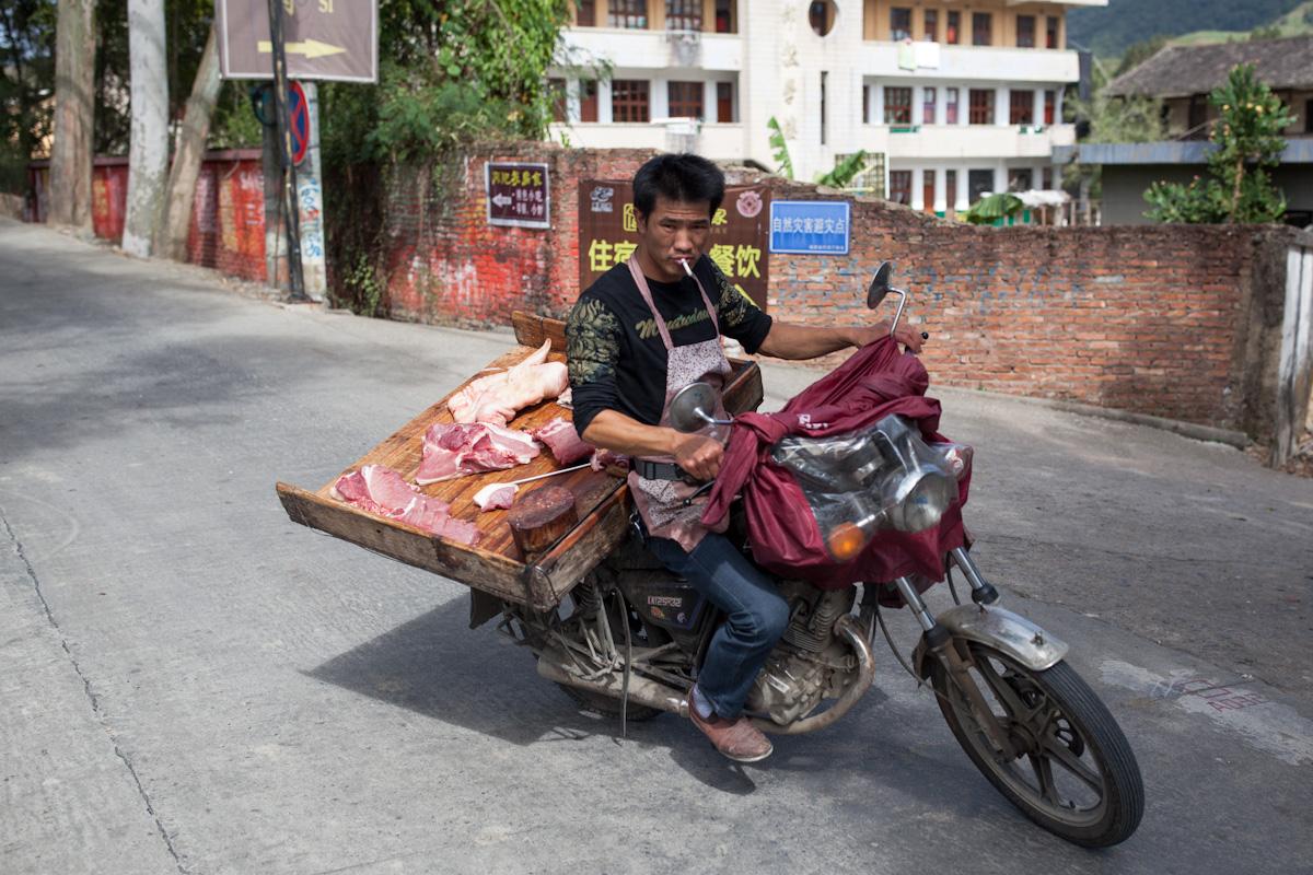 Ein Mann fährt vom Stand einer Fleischerei an einer Straße im Dorf weg, die er gerade beliefert hat. Yunshuiyao - Fujian - China