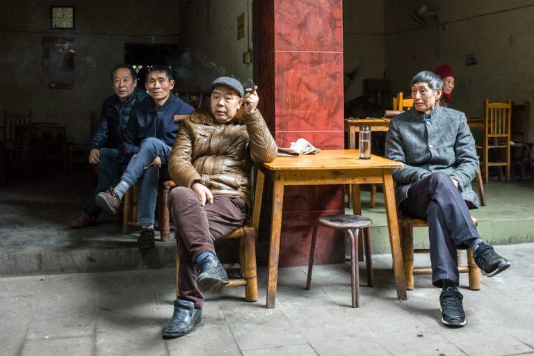 Mehrere Männer sitzen mittags in und vor einem Lokal in Qianwei und beobachten das Geschehen davor. Die Einrichtung des Lokals besteht nahezu nur aus Tischen und Stühlen und letztere aus Bambus gefertigt sind. Qianwei - Sichuan - China