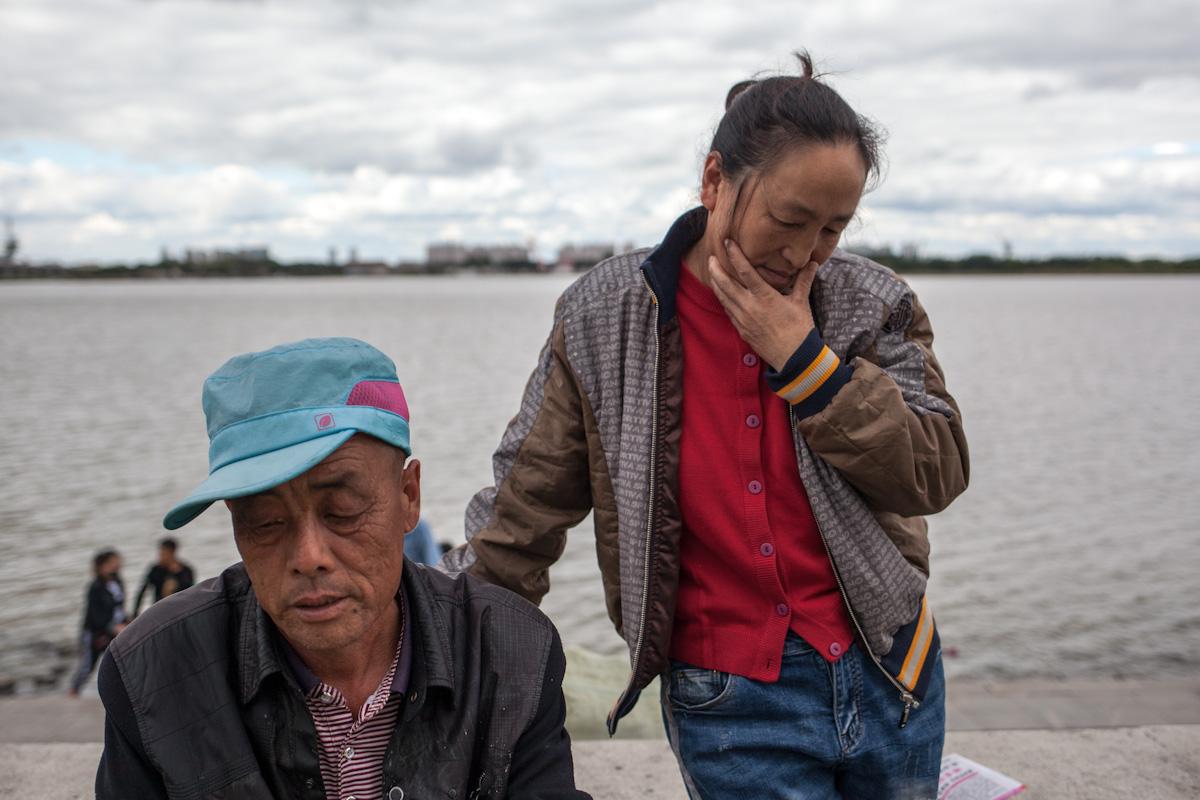 Maisverkäufer am Fluss Songhua in Harbin. Auf einem selbstgebauten Grillrost bereiten die Frau und der Mann Mais zu. Harbin - Heilongjiang - China