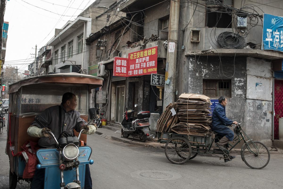 Ein Mann schaut einem anderen Mann nach, der mit seinem Dreirad gebrauchte Kartons sammelt. Xian - Shaanxi - China