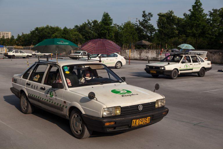 Fahrschüler üben auf einem Fahrschulplatz in Hangzhou. An den Autos sind außen Schirme angebracht. Diese sollen den Begleiter, der neben dem Auto mitlaufen kann, vor der Sonneneinstrahlung schützen. Hangzhou - Zhejiang - China