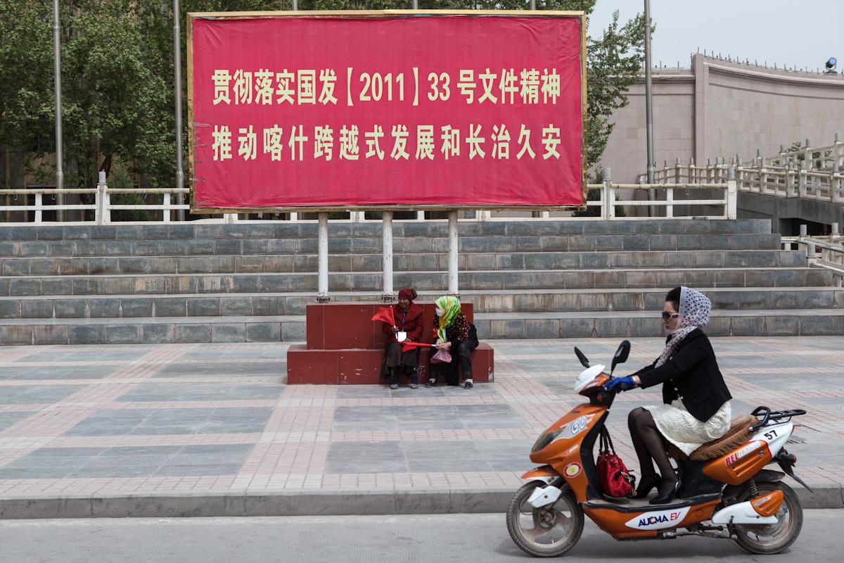 """An vielen Orten befinden sich verschiedenste Plakate und Aufrufe. Das Plakat an einer Straße in Kashgar, im Süden der Provinz Xinjiang, ruft dazu auf: """"Den Geist vom Guofa, Staatratsdokument, (2011) Nr. 33 umsetzen und Kashis sprunghafte Entwicklung und dauerhaften Frieden fördern"""". Kashgar - Xinjiang - China"""