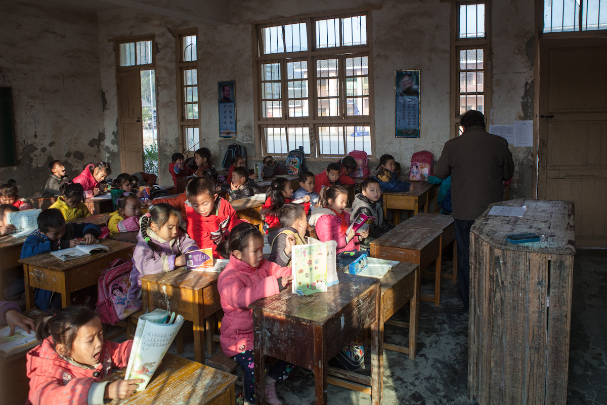 Ein Lehrer unterrichtet eine Schulklasse in einem Dorf auf dem Land. Jeder Schüler hat einen kleinen Tisch für sich, die eng aneinander stehen. Chengyang - Guangxi - China