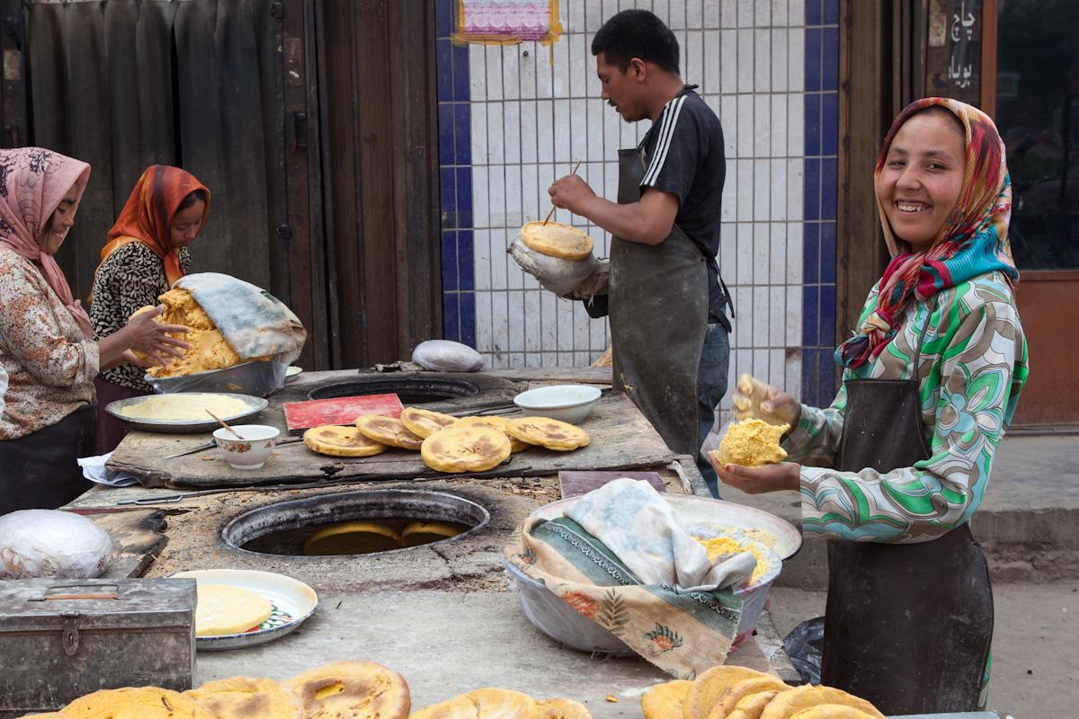 Mehrere Frauen und Männer bereiten Maisfladen zu und backen diese in einem Backofen auf der Straße. Hotan liegt im Süden der Provinz Xinjiang, in der Uiguren die größte ethnische Bevölkerungsgruppe bilden. Hotan - Xinjiang - China