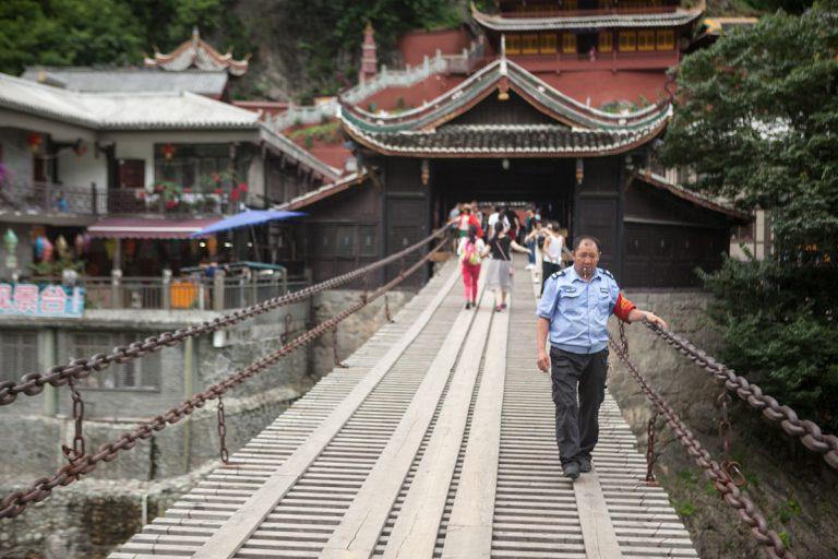 Eine Mitarbeiter wacht über die Touristen auf der Luding-Brücke. Die Hängebrücke, die durch den Langen Marsch 1935 bekannt wurde, ist über 100 m lang und führt 14 m über den Fluss Dadu. Luding - Autonome Präfektur Garzê Tibet - China