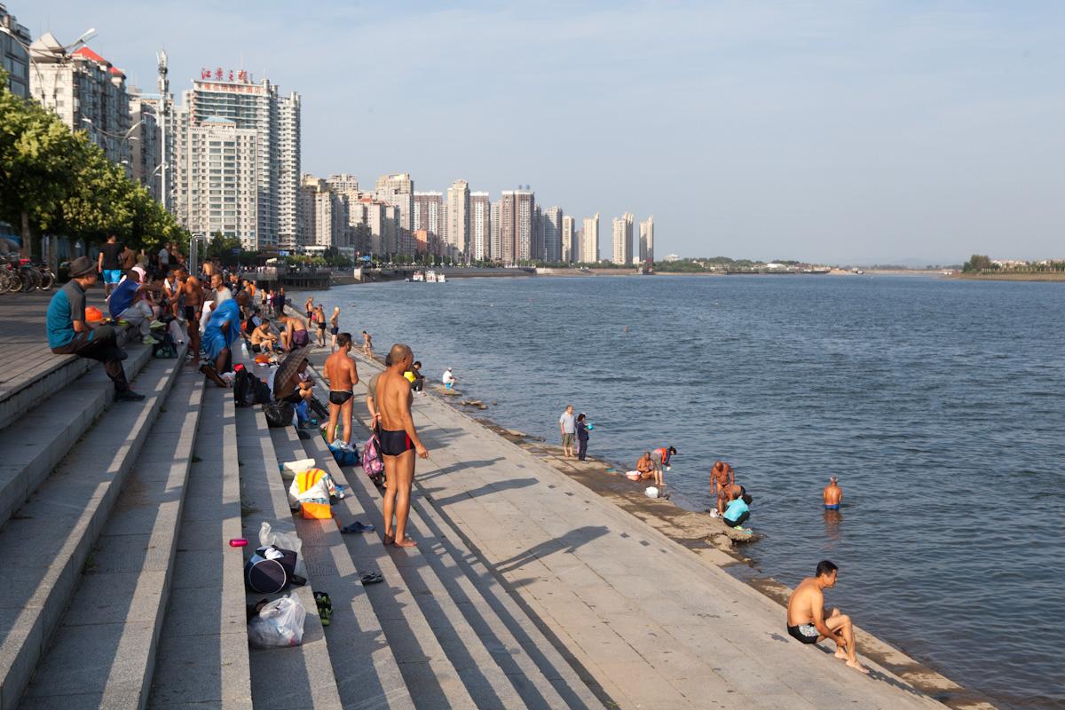 Die Strandpromenade am Fluss Yalu in Dandong wird auch gleichzeitig zum baden genutzt. In der Mitte des Flusses Yalu verläuft die Grenze zu Nordkorea. Dandong - Liaoning - China