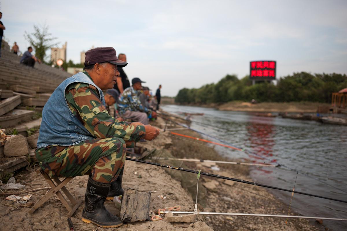 Mehrere Männer sitzen zum angeln am Fluss Yalu in der Nähe von Dandong. Dandong ist eine Grenzstadt zu Nordkorea, gegenüber von Sinuiju. Dandong - Liaoning - China