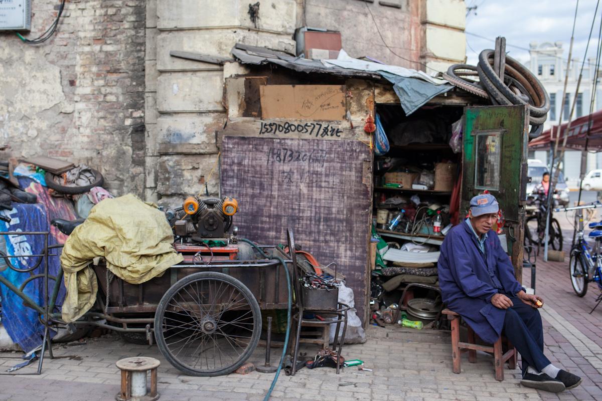 An das Gebäude hat der Mann einen kleinen Schuppen aus Holz angebaut, in dem sich seine Werkstatt befindet. Davor sitzend wartet er auf Kundschaft, um Fahrräder zu reparieren. Harbin - Heilongjiang - China