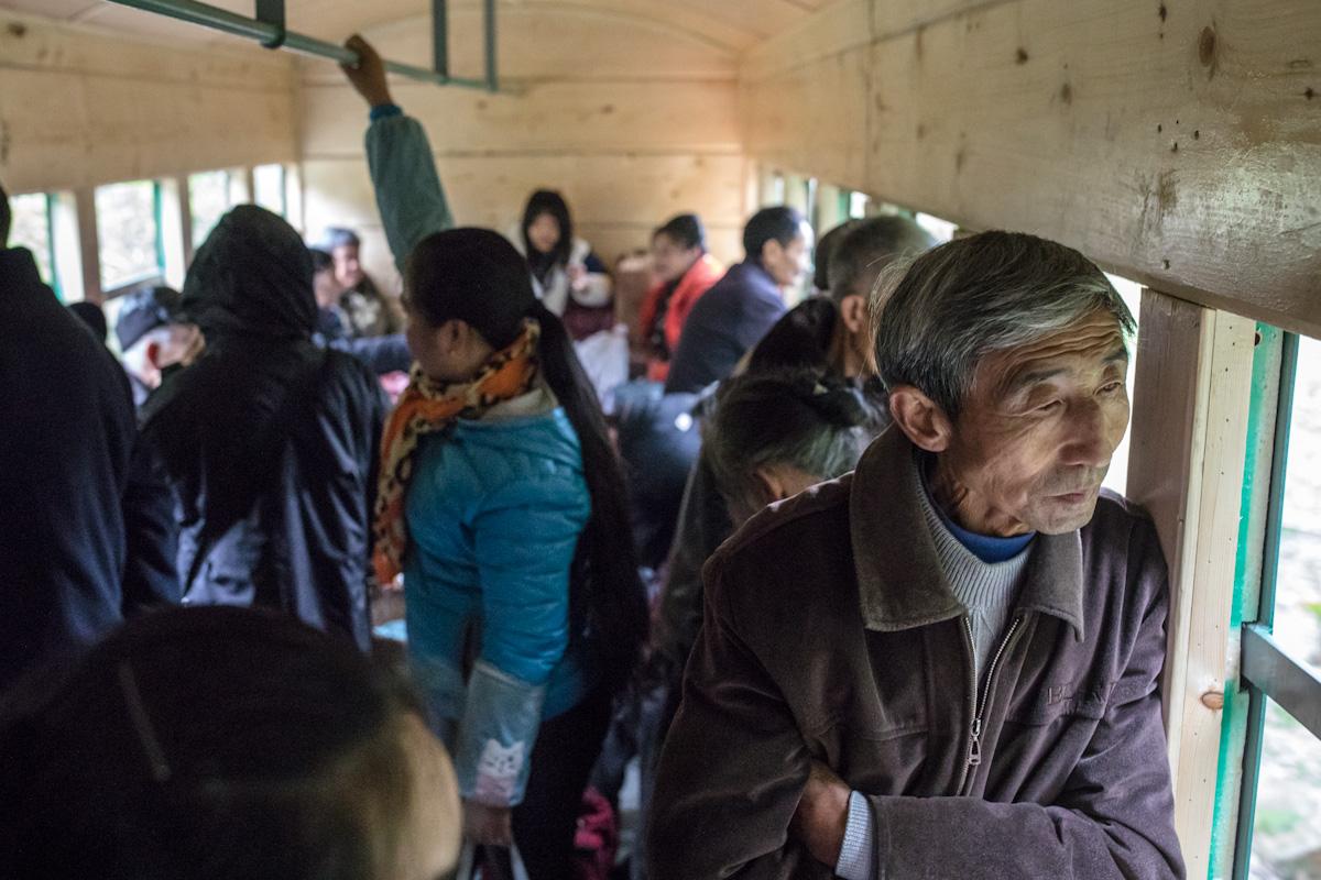 Passagiere schauen aus dem Zug, der mit jeder Station voller wird. Yuejin Bagou - Sichuan - China