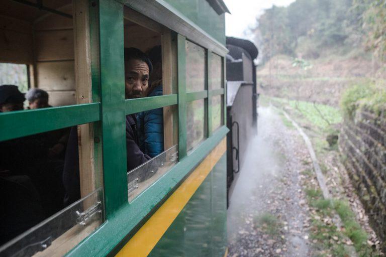 Ein Passagier schaut aus der Zug, der gerade aus einem Tunnel rausfährt. Yuejin Bagou - Sichuan - China