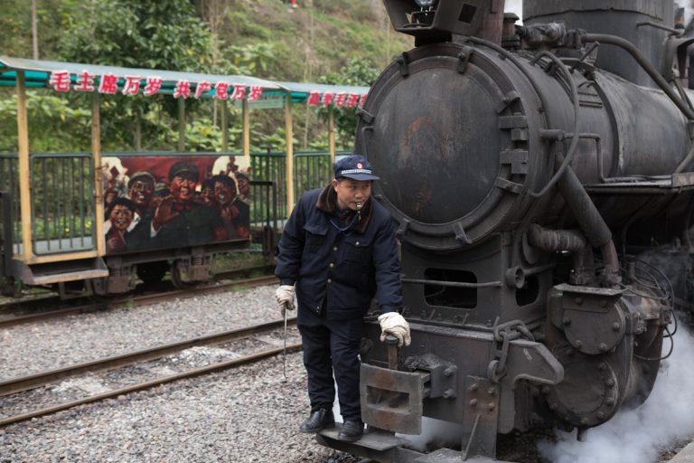 Ein Eisenbahner bereitet im Bahnhof in Bagou eine kohlebetriebene Dampflok für die Fahrt vor. Bagou - Sichuan - China