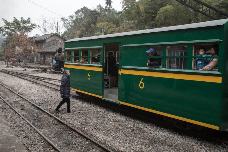 Eine Anwohnerin steigt in Mifengyan in den Zug nach Bagou. Der Zug hält zwischen den Gleisen.