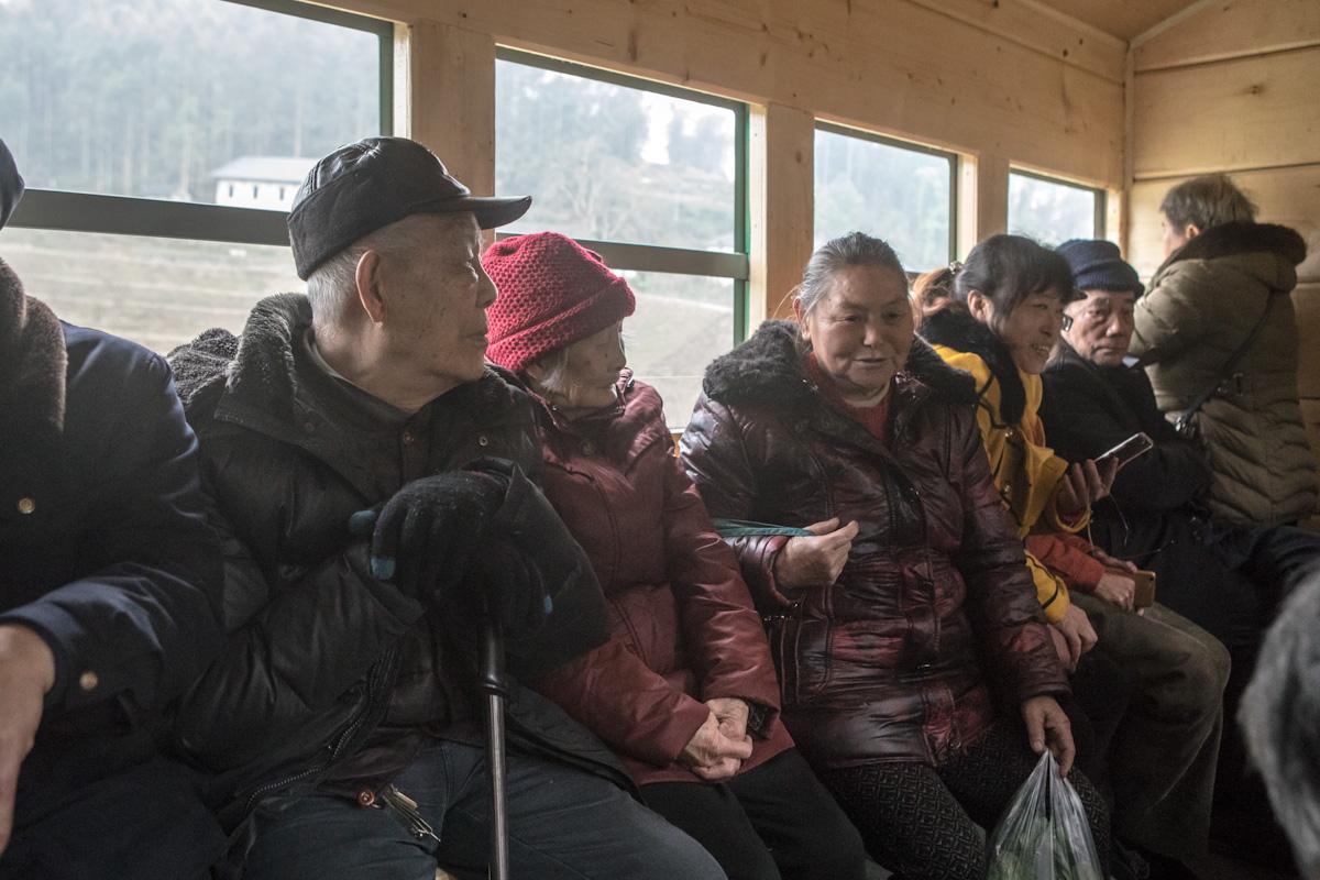 Mehrere Passagiere unterhalten sich, während der Fahrt mit dem Zug. Yuejin Bagou - Sichuan - China