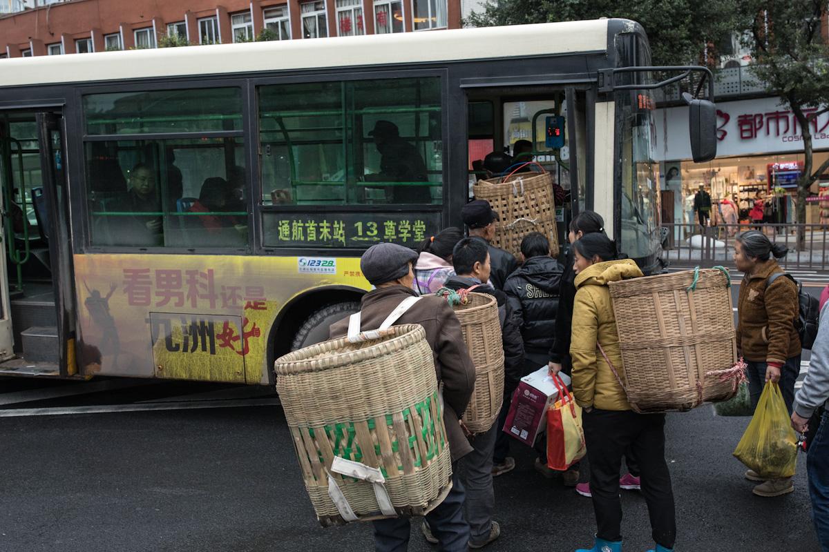 Lokale Anwohner fahren vom Wochenmarkt in Zigong, mit dem Bus zurück in das Dorf Aiye. Für den Transport tragen sie auf dem Rücken große Körbe aus Bambus. Zigong - Sichuan - China
