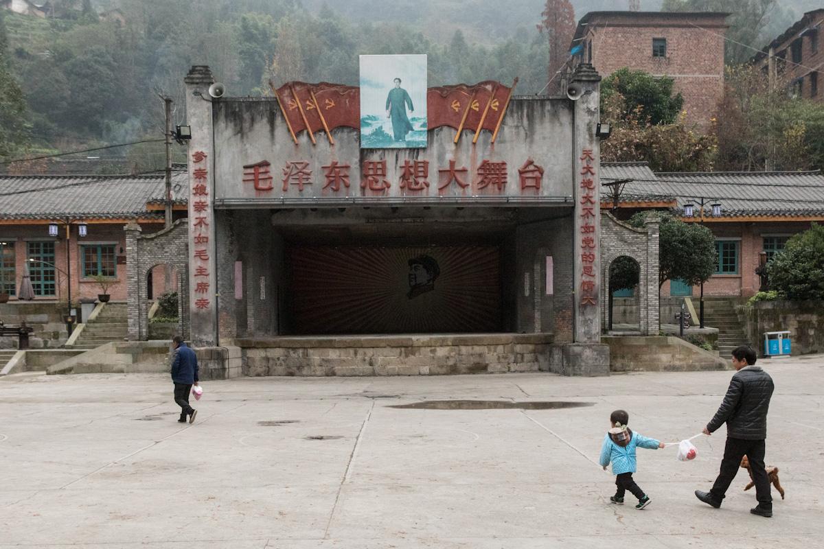 """Eine Familie geht über den Dongfanghong-Platz in Bagou, an dem sich """"Die Große Bühne von Mao Zedong"""" befindet. Über der offenen Bühne ist ein großes Bild von Mao Zedong weithin sichtbar, das mehrere Nationalflaggen Chinas ziert. Die Architektur des Dorfes steht für die Zeit der Kulturrevolution. Bagou - Sichuan - China"""