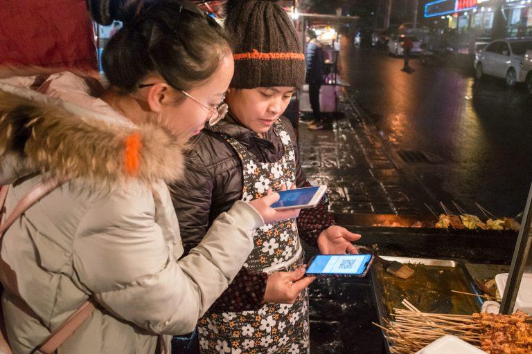 Eine Kundin bezahlt an einem Imbissstand ihr Abendessen mit dem Smartphone und WeChat Pay. Guiyang - Guizhou - China