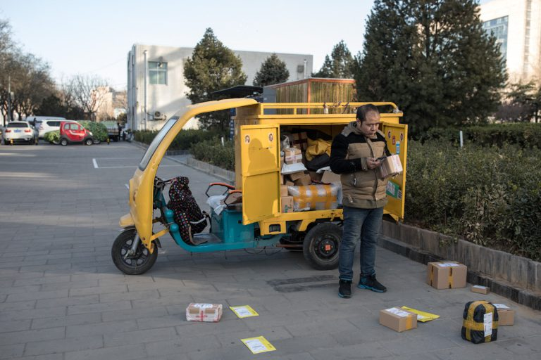 Ein Mitarbeiter eines Lieferdienstes sortiert seine Sendungen vor. Peking - China