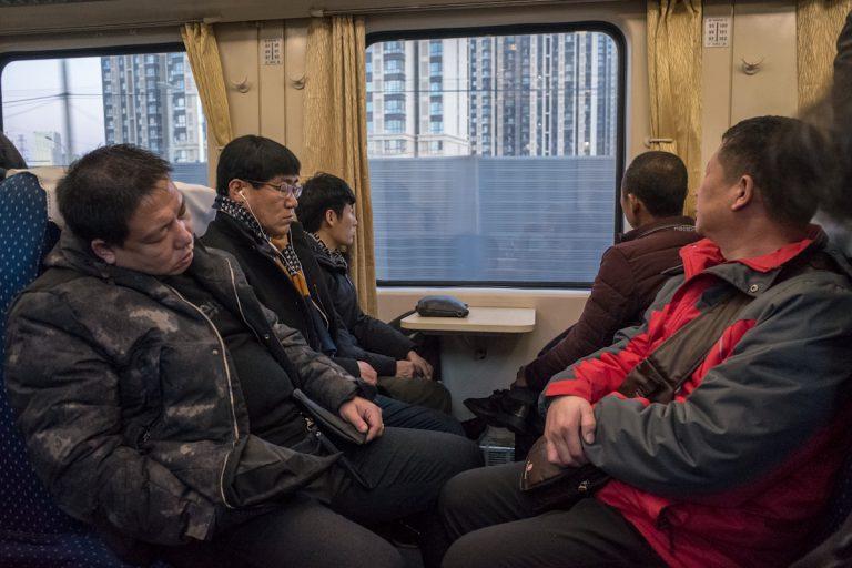 Passagiere schauen im morgendlichen Berufsverkehr in Peking aus dem Zug, auf eine neu errichtete Hochhaussiedlung. Peking - China