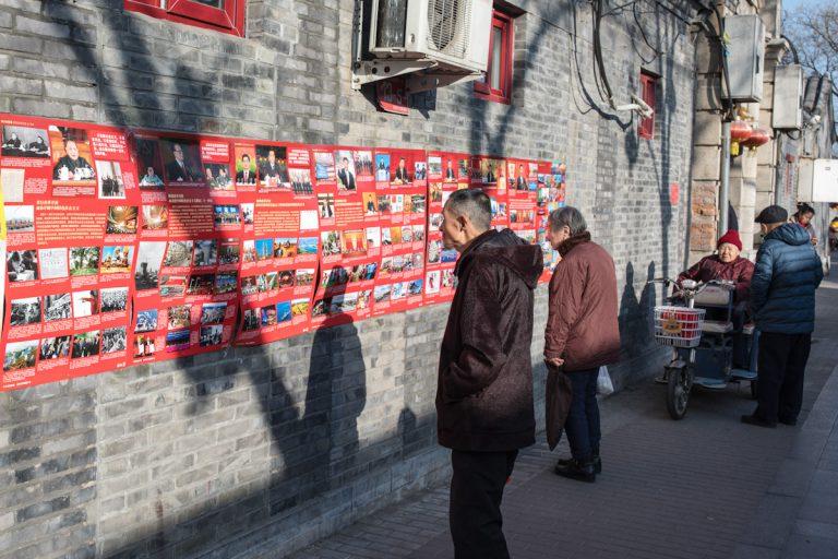 Mehrere Anwohner lesen an einer öffentlichen Wandzeitung, an einer Hauswand in Peking. Anläßlich des 40. Jahrestages der wirtschaftlichen Öffnung Chinas am 18.12.2018, zeigen viele Artikel und Bilder die damalige und aktuelle Entwicklung Chinas. Peking - China