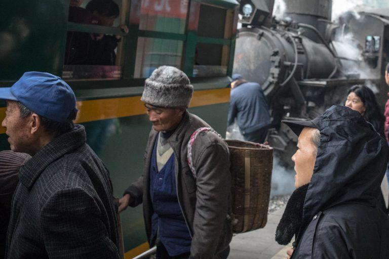 Mitfahrende steigen in Yejin in den Personenwaggon, während ein Eisenbahner die Dampflok ankoppelt. Yuejin Bagou - Sichuan - China