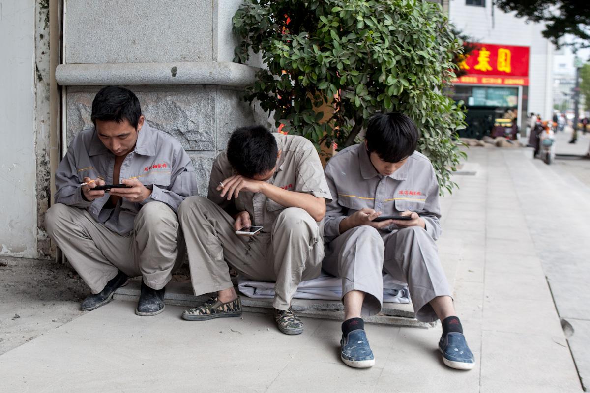 Drei Arbeiter einer Fabrik sitzen vor dem Eingang und verbringen die Mittagspause vertieft mit ihrem Smartphone. Fuzhou - Fujian - China
