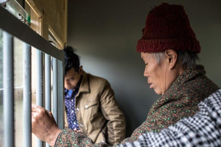 Eine Frau hält sich an den Gitterstäben fest, womit die Tür vom Personenwaggon verschlossen wird. Yuejin Bagou - Sichuan - China