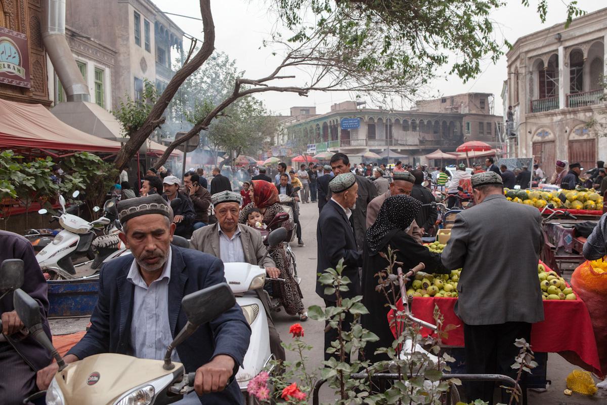 Mehrere Bewohner durchqueren mit ihrem Mofa einen Markt in der Altstadt in Kashgar. Der Markt wird von vielen Anwohnern für den täglichen Bedarf genutzt. Kashgar - Xinjiang - China