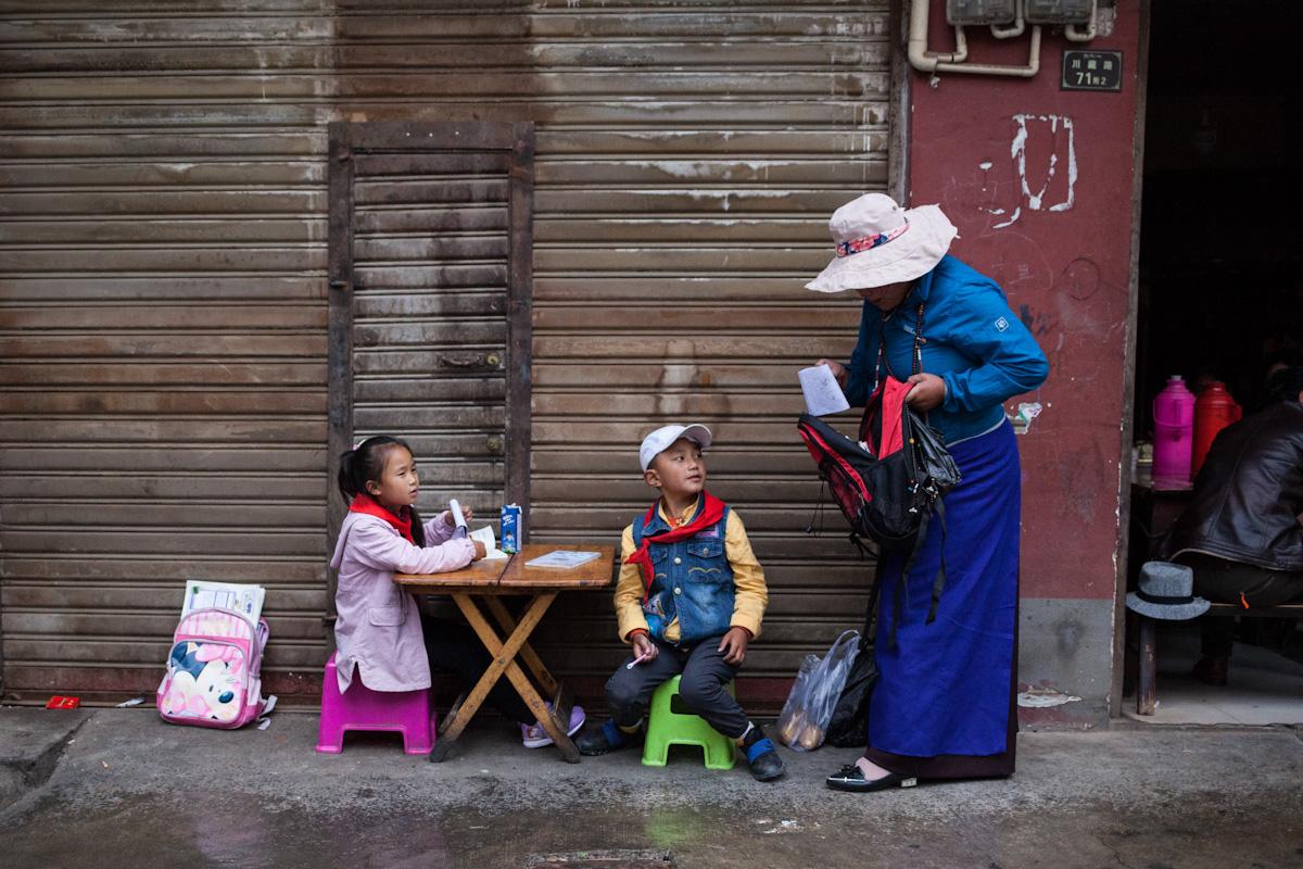 Die beiden Kinder sitzen draußen an der Straße in Garzê an einem kleinen Tisch und machen Hausaufgaben. Ein Frau holt aus dem Schulrucksack des Jungen weitere Unterlagen heraus. Das Mädchen hat ein tibetisches Schulbuch und schreibt später in ihren Schulblock.  Garzê - Autonome Präfektur Garzê Tibet - China