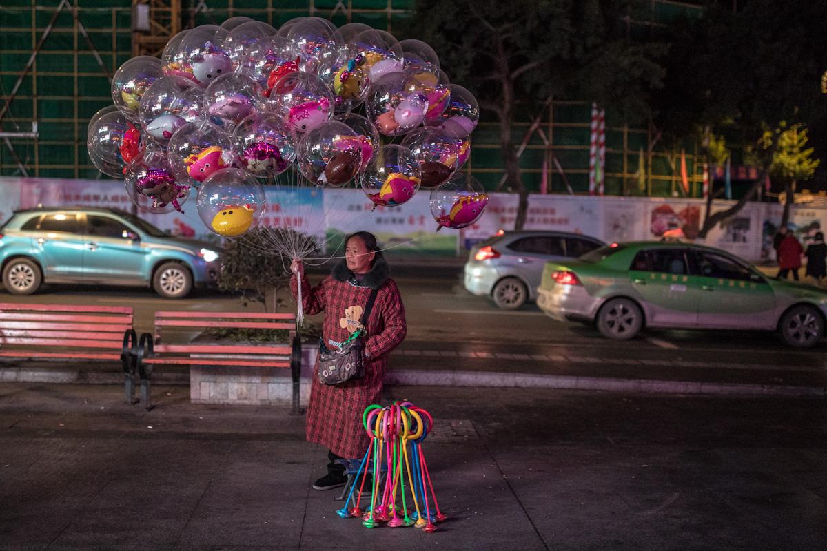 Eine Frau verkauft abends auf der Straße transparente Luftballons, die Innen verschiedene bunte aufgeblasenen Figuren beinhalten. Zigong - Sichuan - China