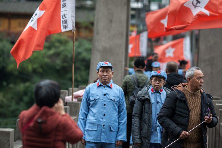 Chinesische Besucher tragen Uniformen der Roten Armee für einen Gang über die Hängebrücke in Bing'an. Darüber führte unter Mao Zedong der lange Marsch 1934/35. Bing'an - Guizhou - China