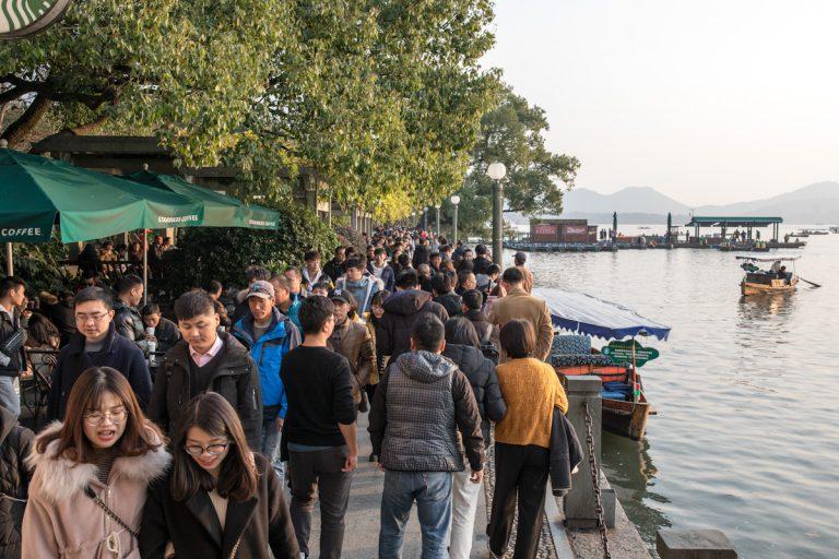 Die Promenade am Seeufer des West Lake in Hangzhou ist am Wochenende sehr gut besucht. Viele Menschen nutzen das warme Winterwetter für einen Spaziergang am See. Hangzhou - Zhejiang - China