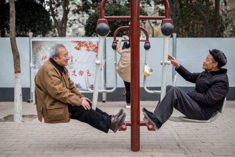 Zwei Pensionäre unterhalten sich beim Frühsport im Lianhu Park. Die Frau am Sportgerät dahinter, hebt ihre Beine bis zur oberen Stange. Xi'an - Shaanxi - China