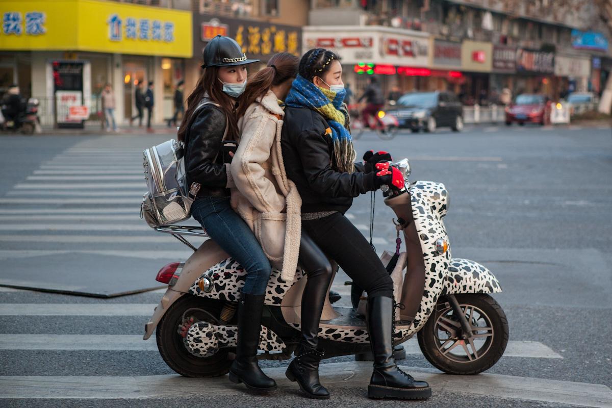 Drei Frauen sind gemeinsam auf einem bunten Mofa unterwegs. Warm angezogen warten sie gerade an einer Kreuzung. Hangzhou -Zhejiang - China