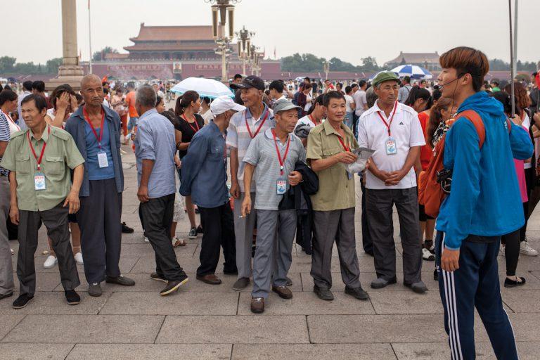 Ein Reiseführer spricht zu seiner Reisegruppe auf dem Platz des Himmlischen Friedens, die woanders hinschaut und kaum zuzuhören scheint. tiananmen platz square Peking - China