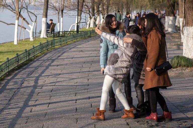 Mehrere junge Frauen fotografieren sich selbst im Park am Seeufer des West Lake. Hangzhou - Zhejiang - China