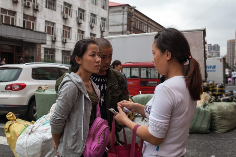 Eine Frau und ein Mann mustern eine andere Frau auf einem Großmarkt in Harbin, auf dem Bekleidung verkauft wird. Für den Transport wird diese stark komprimiert und in großen Säcken abgepackt. Harbin - Heilongjiang - China