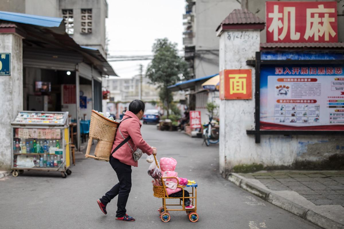 Eine ältere Frau schiebt ein Kleinkind in einem traditionellen chinesischen Kinderwagen. Zusätzlich trägt sie auf dem Rücken einen Kinderkorb, hergestellt aus Bambus. Chengdu - Sichuan - China
