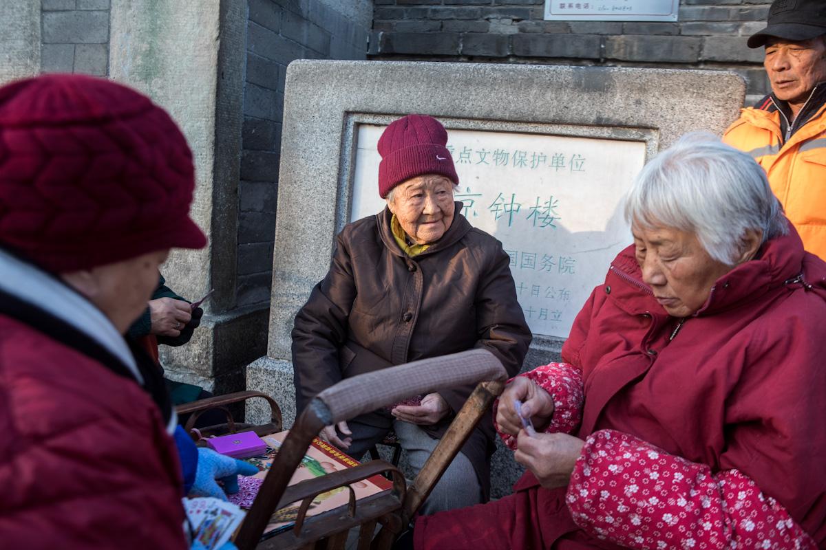 Ältere Pensionäre spielen Karten, an einem sonnigen Tag im Winter, in einem Hutong nahe der Verbotenen Stadt. Peking - China