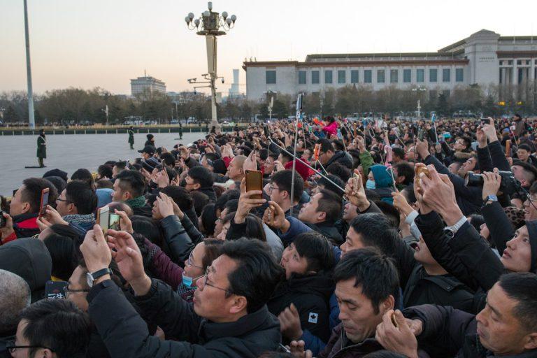 Besucher auf dem Platz des Himmlischen Friedens sehen sich die Zeremonie zum Hissen der Nationalflagge Chinas an. Peking - China
