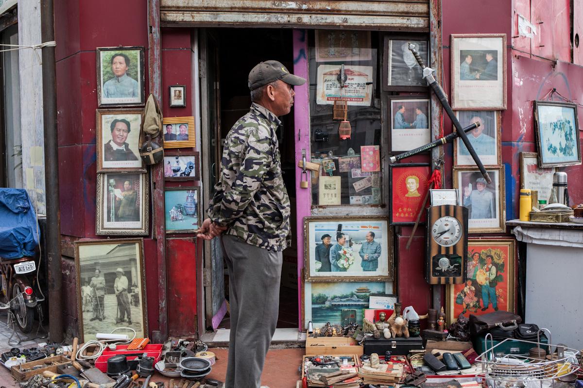 Ein Verkäufer steht vor seinem Geschäft mit Antiquitäten, wovon ein größerer Teil gerahmte Bilder mit Motiven von Mao Zedong einnimmt. Harbin - Heilongjiang - China